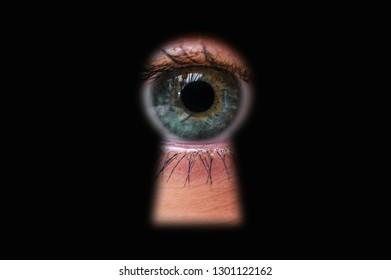 Human eye behind door looking through a keyhole - voyeurism concept