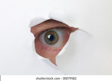 Human eye looking through a hole in white paper