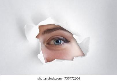 Human eye through the hole of the white paper, spy eye