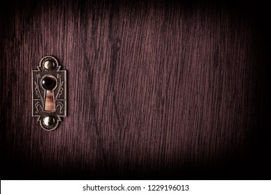 A human eye watching through an old keyhole