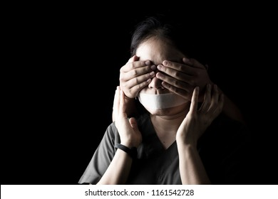Human eyes are blinded by others in the darkness background, Was blindfolded, gagged. Independence, Compulsion and Obscurity concept