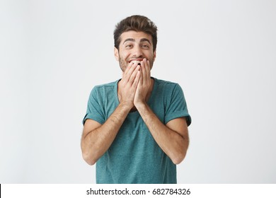 Human face expressions, emotions and feelings. Astonished and surprised bearded young man in blue t-shirt pointing at blank studio wall, telling that he has an idea