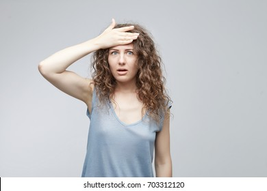 Human face expressions and emotions. Forgetful white-skinned woman holding hand on her head with a painstaking expression as she struggling to remember something. Cute female student slapping forehead