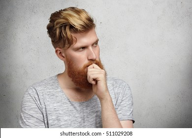 Human face expressions and emotions. Young puzzled fashionable student in gray t-shirt thinking of something important, stroking or touching his thick beard and looking away at blank concrete wall