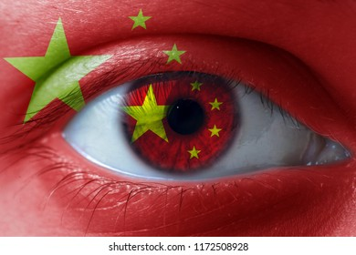 Human face painted with flag of China on the face and the iris. The concept of the chinese view of life.