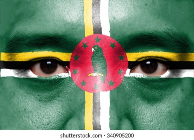 Human face painted with flag of Dominica.