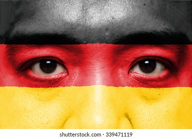 Human face painted with flag of Germany.