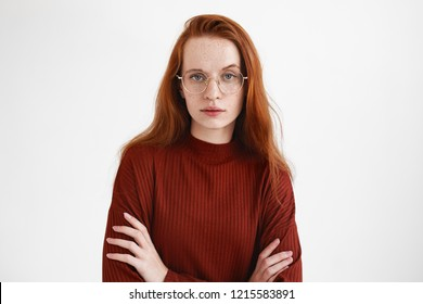 Human facial expressions and body language. Studio shot of displeased skeptic young Caucasian woman with long ginger hair and freckles keeping arms folded, having distrustful suspicious look