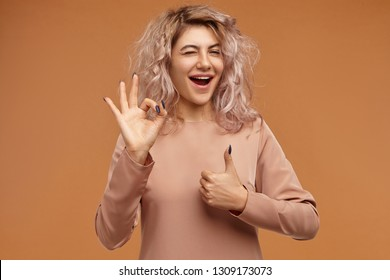 Human facial expressions and body language. Horizontal image of stylish fashionable young Caucasian female with messy pinkish hair exclaiming with excitement, making ok gesture and showing thumbs up