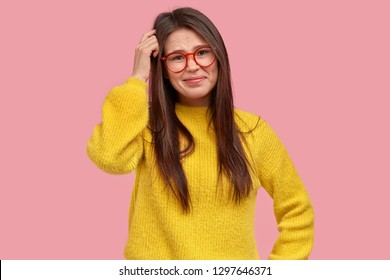 Human facial expressions concept. Confused attractive young Asian woman scratches head, has amnesia, frustrated look, wears optical glasses and yellow clothes, isolated over pink background.