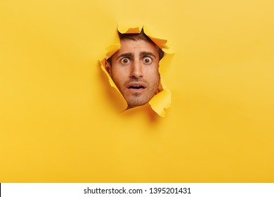 Human facial expressions concept. Worried young man with dark eyes, bristle, frowns eyebrows, has scared look, gazes through paper hole, feels nervous and puzzled. Yellow background with blank space