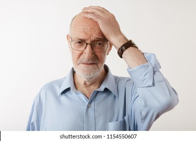Human facial expressions, feelings, emotions and reaction. Horizontal sudio shot of sad unhappy mature man wearing shirt, watch and eyeglasses holding head, being upset with unpleasant news