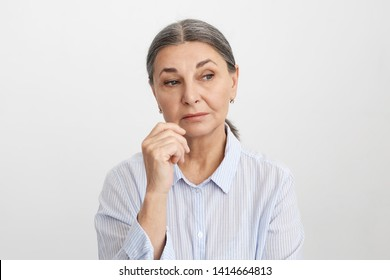 Human facial expressions, feelings and emotions. Sad or thoughtful attractive senior female dressed in striped blue shirt holding hand at her face, having pensive deep in thoughts look, pondering