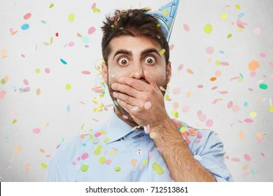 Human facial expressions, feelings, reaction and attitude. Puzzled terrified young European man in holiday cap covering mouth in shock because he forgot to buy present on his friend's birthday