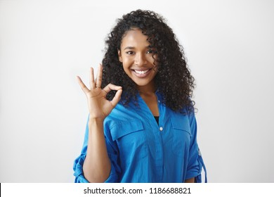 Human facial expressions, signs, symbols and gestures. Picture of emotional charming young African American woman with happy cheerful smile, making ok gesture, saying that she is doing great
