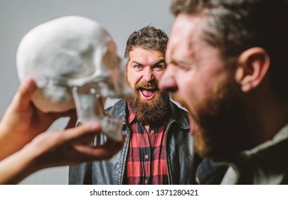 Human fears and courage. Looking deep into eyes of your fear. Man brutal bearded hipster looking at skull symbol of death. Overcome your fears. Be brave. Focused on breaking fear. Psychology concept.