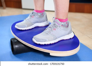 Human feet in jogging shoes standing on a balance board