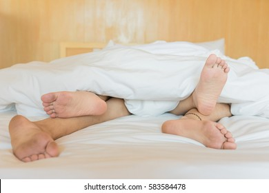 Human feet sleep together and make love in the bedroom