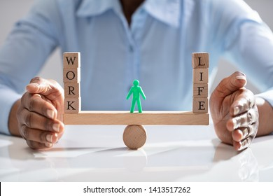 Human Figure Standing Between Work And Life Wooden Blocks On Seesaw Being Protected By Businesswoman