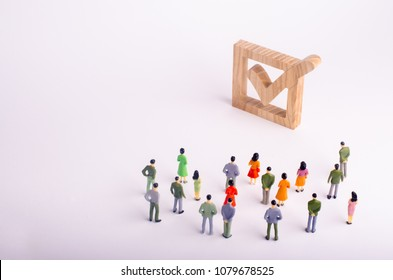 human figures stand together next to a tick in the box. The concept of elections and social technologies. Volunteers, parties, candidates, constituency electorates. Human rights Selective focus