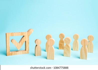 human figures stand together next to a tick in the box. The concept of elections and social technologies. Volunteers, parties, candidates, constituency electorates. Human rights. Selective focus