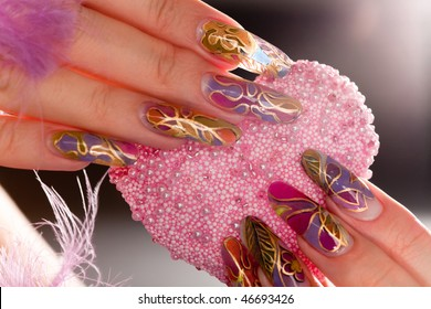 Human fingers with long acrylic fingernail and beautiful manicure holding pink heart