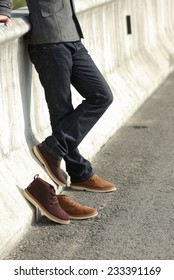 Human foot with brown leather shoes and jeans