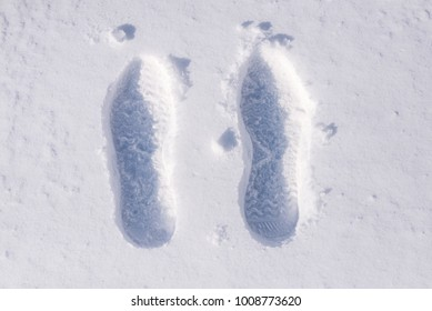 Human footprint in white snow, free space. Footprints from boots in the snow.