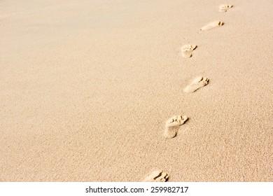 Human footprints on beach sand. Horizontal shot with copy space