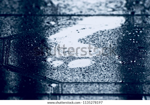 Human footprints on a wet tiles surface isolated blurry photograph