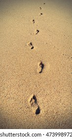 Human footprints in the sand, natural vintage background