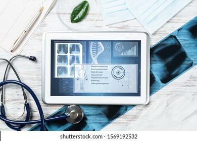 Humane genetische Forschung im medizinischen Labor. Tablet-Computer mit DNA-Helix-Struktur auf dem Bildschirm. Stethoskop, Röntgenbild und Kardiogramm auf Holzschreibtisch. Medizinische Diagnostik und Genomtest des Patienten