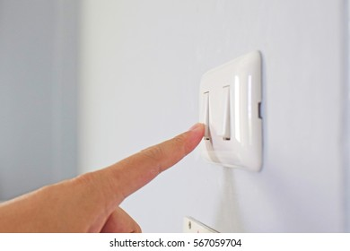 Human going to turn on/off switch at the white wall by index finger