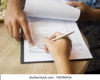 The human hand ,agent of the insurance is point to blank of claim form to the customer for sign name with pen ,on wooden desk,vintage tone.