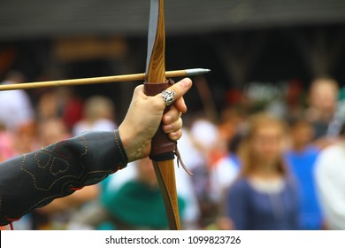 A human hand with big wooden bow and long arrow. Living history festival in a medieval castle. Archery tournament in historical costumes. The Robin Hood legend. Bowman before shooting from a longbow.