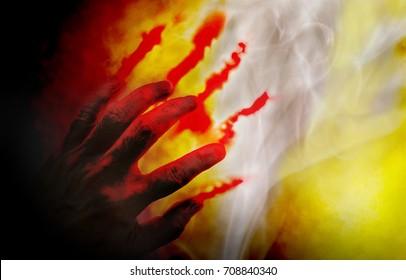 Human hand with blood on dark background.