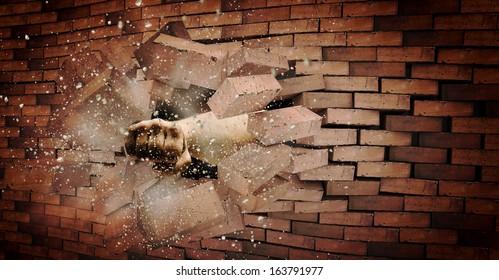 Human hand breaking brick wall. Strength and power