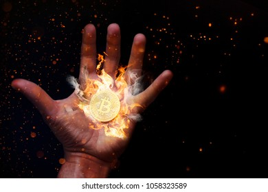 Human hand with a burning bitcoin.