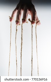 The human hand controls the puppet with the fingers attached to them threads on a white background