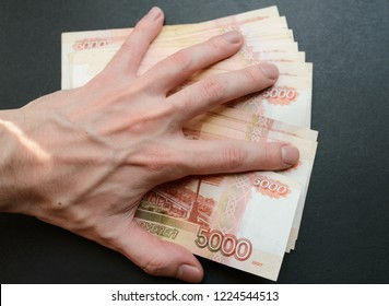Human hand cover five-thousandth banknotes on a dark background.