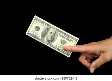 Human hand delivers bill hundred dollars, on a black background