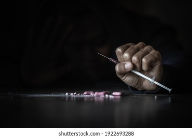 Human hand of a drug addict and a syringe with narcotic syringe lying on the floor. World Anti-drug Day.