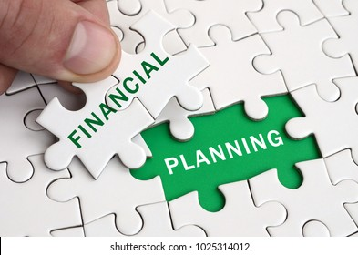 The human hand fills the last missing elements of the surface from the jigsaw puzzle. Image with words financial and planning