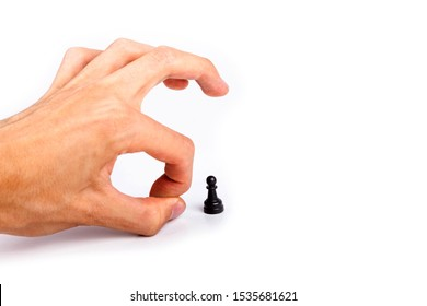 Human hand flicking a chess piece, huge hand flicks away a small tiny black pawn. Flick gesture isolated on white. Danger, anxiety and peer pressure, being fired, losing job due to layoffs concept