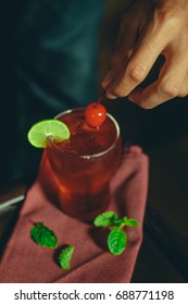 Human Hand Focus Push Red Cherry on Fresh Red Cocktail with Lime