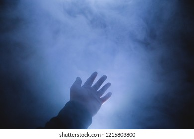 human hand in the fog stretched forward dim light.
