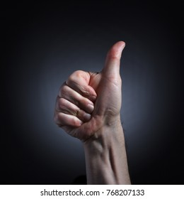 The human hand in a gesture of approval with a raised thumb closeup on dark background.