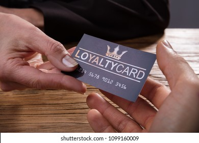 Human Hand Giving Loyalty Card To Another Person Over Wooden Desk