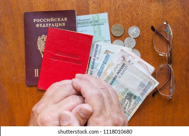 the human hand, glasses, and a pension certificate on wooden surface-the translation into Russian: senior certificate