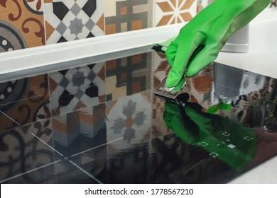Human hand in a glove cleaning a ceramic hob with a scraper